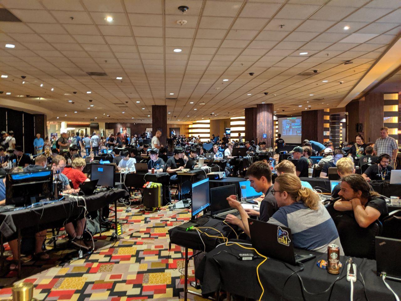 DEF CON 27のCTF決勝会場。多くのハッカーがチーム別のテーブルに分かれ、PCを前に問題に取り組んでいる。